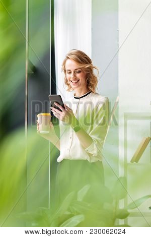 Photo of amazing young business woman in office looking aside chatting by mobile phone drinking coffee.