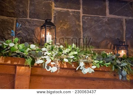 Floral Garland Of Flowers On A Fireplace Mantle At A Wedding Venue Where A Ceremony Will Take Place.