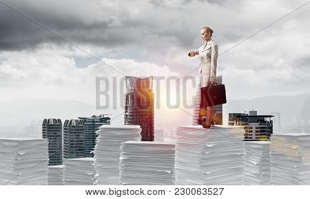 Confident Business Woman In Suit Standing On Pile Of Documents And Looking At Watch With Cityscape A
