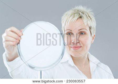 Beautiful middle-aged woman with mirror