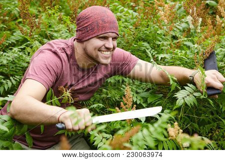 A man with a machete making his way through a thicket, sailor pirate in the jungle