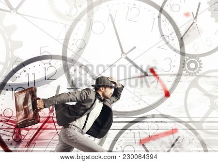 Business Man Runs Fast On A Background Of Clocks