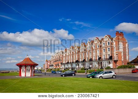 BEXHILL-ON-SEA, UK - JUN 4, 2013: Victorian wooden seafront shelter and buildings at popular seaside resort Bexhill-on-Sea in East Sussex