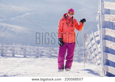 Young Woman In Skiing Suit Is Holding A Snowboard In Background Of Snowy Mountains And Route For Des