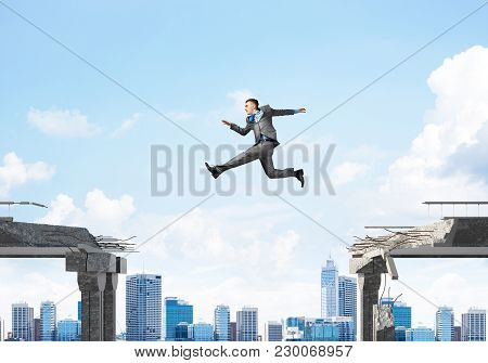 Businessman Jumping Over Gap In Concrete Bridge As Symbol Of Overcoming Challenges. Cityscape On Bac