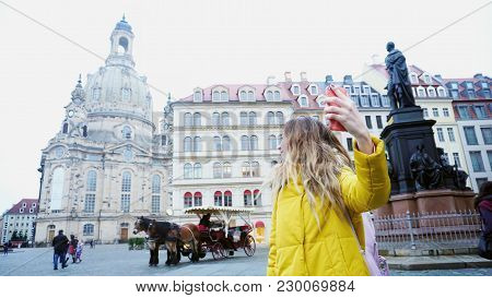Exquisite Young Woman Holding Gadget And Talking On Internet With Friend, Waving Hand At Camera Of S