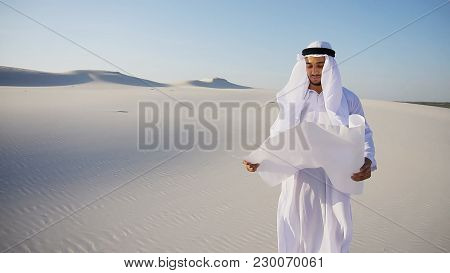 Beautiful Emirate Sheikh Businessman Studying Project Of Future Construction Of Complex, Standing In