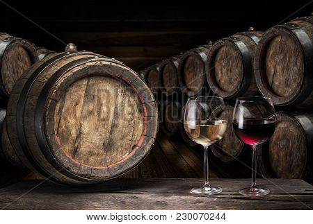 Wine barrel  and two wine glasses on the old wooden table. Wine cellar.