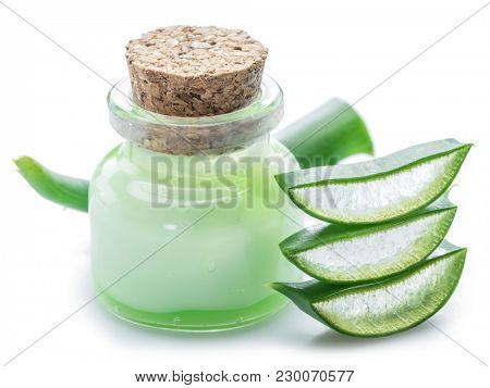 Aloe gel in the cosmetic jar and fresh aloe leaves on white background.