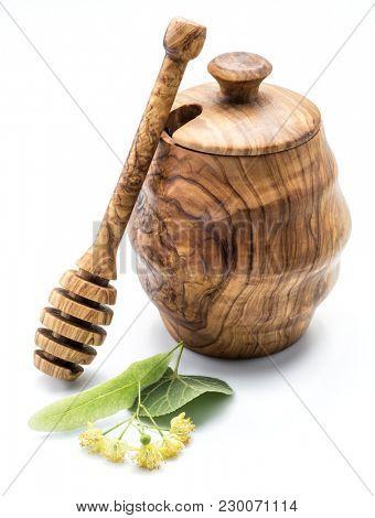 Wooden pot full of fresh linden honey and linden flowers.