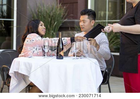 Female Hustler On A Date With A Gullible Man Paying For Her Restaurant Bill In An Outdoor Cafe.  The