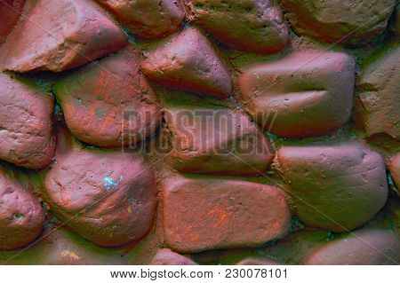 Rock Wall With Large Rounded Stones. Stone Wall Painted With Brown Paint. Stone Background From Foun