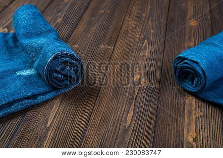 Roll Frayed Jeans Or Blue Jeans Denim Collection On Rough Dark Wooden Table Background With Copy Spa