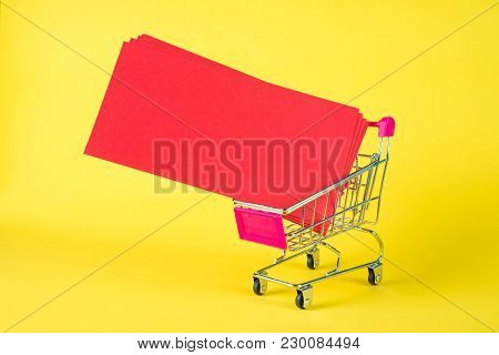 Shopping Cart Or Supermarket Trolley And Blank Red Envelop On Yellow Background With Space For Add T