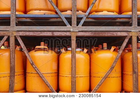 Used Gas Butane Cylinder Containers In Orange Tone. Horizontal