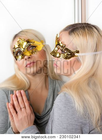 A Woman In A Golden Carnival Mask, Glasses Looks Up Standing In Front Of A Mirror
