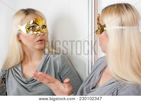 The Masked Woman Stares At Her Reflection In The Mirror.