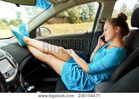 Girl In Car Sitting On Passenger Seat With Feet On Car Dashboard And Talking On Mobile Phone. Young