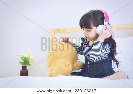 Cute Little Girl With Headphones On The Bed.family And Relaxing Concept.