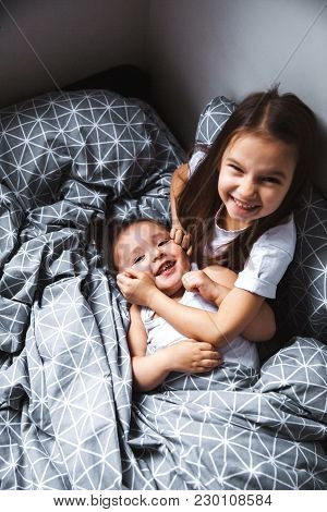 Little Sister Hugging Her Baby. Toddler Kid Meeting New Sibling. Cute Girl And New Born Baby Boy Rel