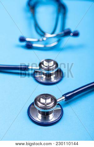 Close Up Image Of Two Stethoscopes Lying On Blue Background