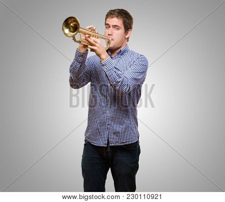 Cute Man Blowing Trumpet against a grey background