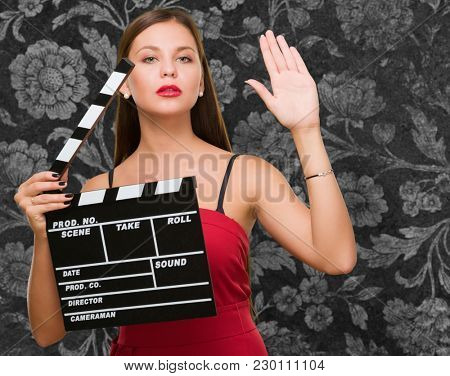 Young Woman Holding Clapper Board against a vintage background