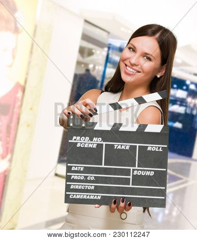 Portrait Of A Young Woman Holding Clapboard in a shop