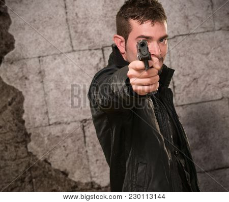 man with leather jacket pointing with gun against an old rusty background