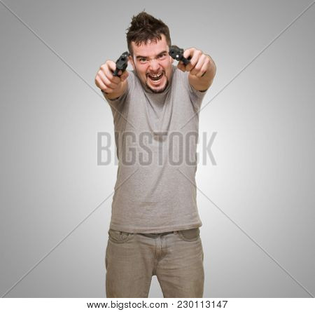 angry man aiming with guns against a grey background