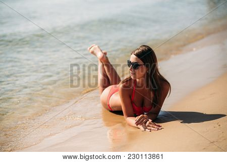 Beautiful Girl In A Pink Bathing Suit, In The Sea. Sunny Weather. Summer.