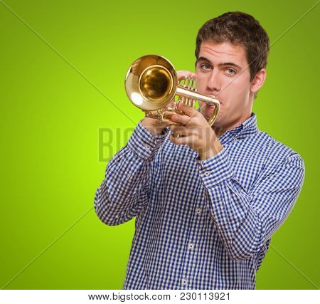 Young Man Blowing Trumpet against a green background