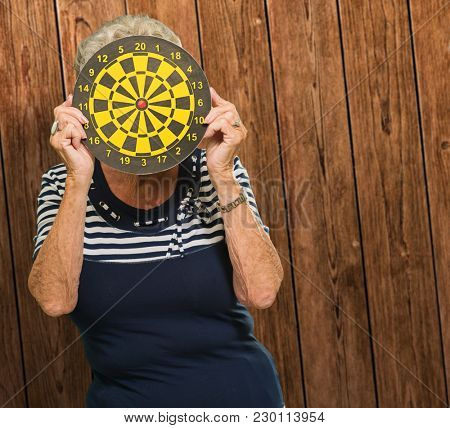 Woman Hiding Her Face With Dart Board On Wooden Background