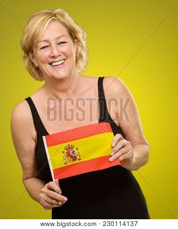 Happy Mature Woman Holding Spain Flag Isolated On Colored Background