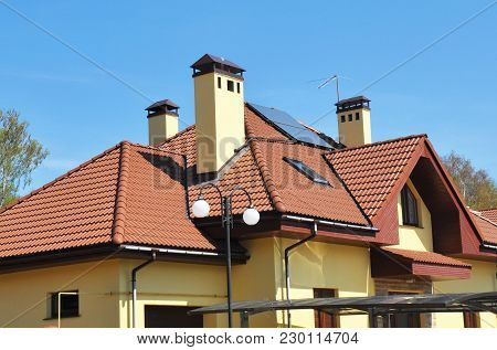 Modern House Attic Roof With Skylight Windows, Roof Gutter, Chimneys And Solar Panels.
