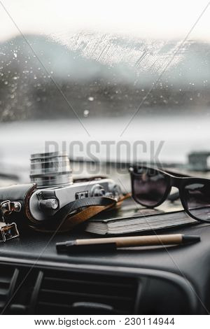Notebook, Glasses And Film Camera On The Dashboard In The Car. Closeup Shot. Vertical