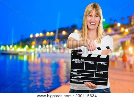 Happy Woman Holding Clapper Board at a port
