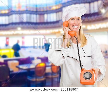Female Chef Holding Telephone in a restaurant