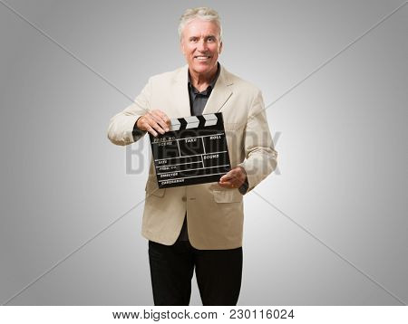 Mature Man Holding Clapper Board against a grey background