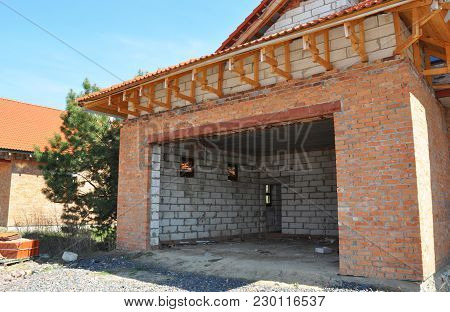Building Construction New Unfinished  House Garage.  Roofing And Insulation Brick Wall Garage.