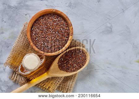 Flax Seeds In Bowl, Wooden Scoop And Flaxseed Oil In Glass Bottle On Homespun Napkin Over Light Text