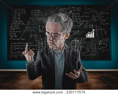 Teacher Explaining Math Formulas In Classroom Holding A Laptop, In Front Of The Blackboard Full Of M