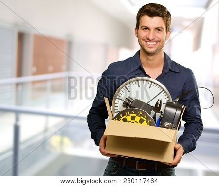 Portrait Of Happy Man Holding Cardboard Box, Indoors