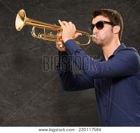 Young Man Holding Trumpet On Wall
