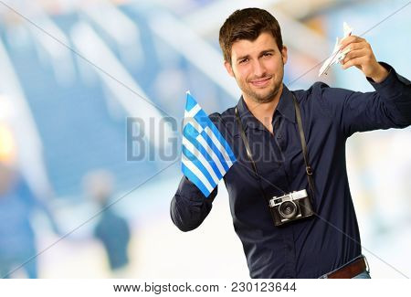 Photographer Holding Greece Flag And Miniature Airplane, Indoor
