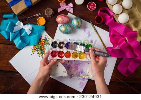 Preprimary Painting Of Easter Eggs, Brushes, Paints, Eggs, Sweets, Ribbons On The Dark Wooden Table.
