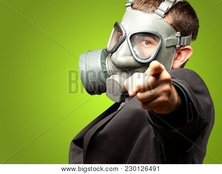 Businessman Pointing With Gas Mask against a green background