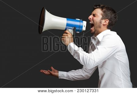 Portrait Of A Man Yelling Into A Megaphone Against black