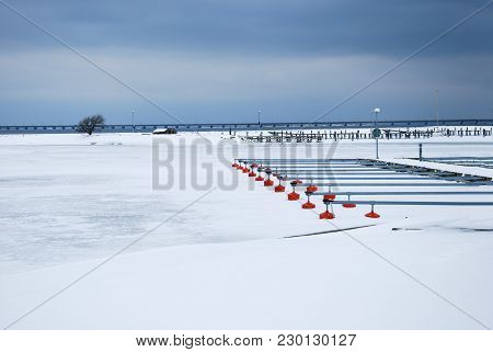Ice Covered Small Boat Harbor With Red Buoys