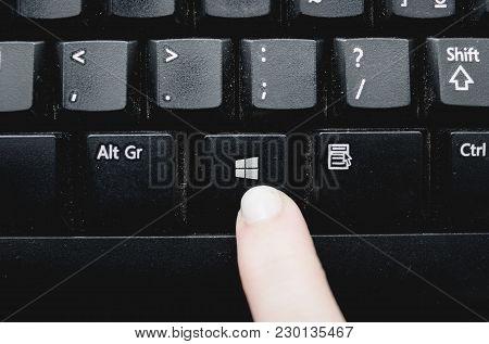 Brazil - March 02, 2018: Finger Pressing The Windows Key From A Dusty Black Keyboard.